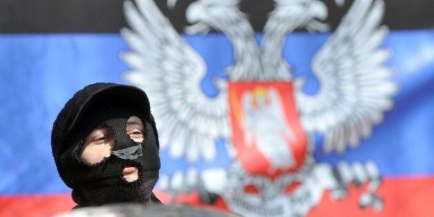 Pro-Russia activists stands in front a so-called Donetsk Republic flag as they guard a barricade outside...