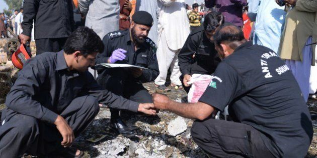Pakistani security officials collect evidence at the site of a bomb explosion in a fruit and vegetable...