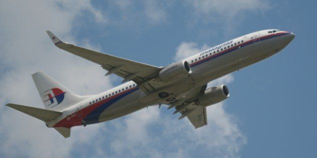This picture taken in Tangerang on March 18, 2013 shows a Malaysia Airlines Boeing 737 plane flying over...