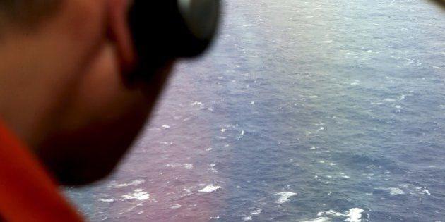 Kazuhiko Morisawa looks out of a window of a Japan Coast Guard Gulfstream aircraft during the search...