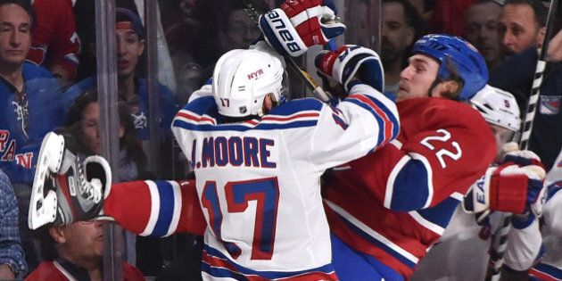 MONTREAL, QC - MAY 27: John Moore #17 of the New York Rangers checks into the boards Dale Weise #22 of...