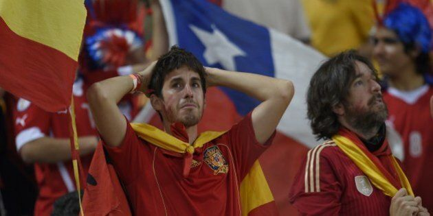 Spain's fans react after the Group B football match between Spain and Chile in the Maracana Stadium in...