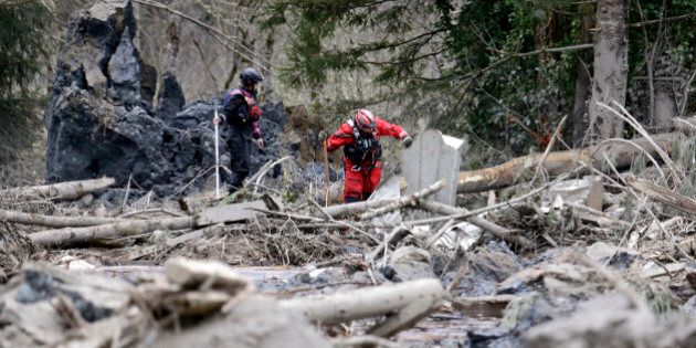 Searchers slowly move through a field of debris following a deadly mudslide, Tuesday, March 25, 2014,...