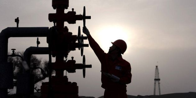 A worker checks pipes at PetroChina's Tarim Oilfield in Taklamakan Desert, in China's western Xinjiang...