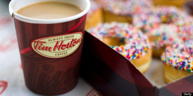 A cup of Tim Hortons Inc. coffee and doughnuts are arranged for a photograph in Toronto, Ontario, Canada,...