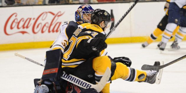 BOSTON, MA - APRIL 12: Torey Krug #47 of the Boston Bruins collides into Matt Hackett #31 of the Buffalo...