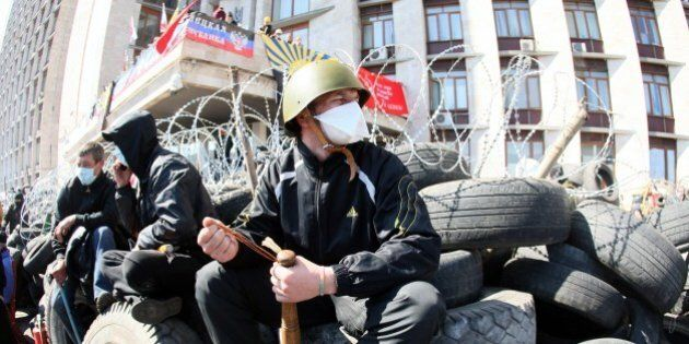 A pro-Russian militant holding a bat guards a barricade in front of the Donetsk regional administration...