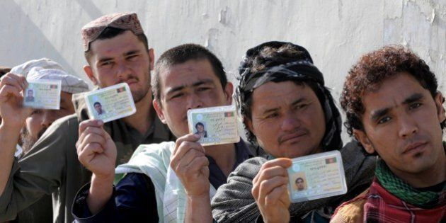 Afghan voters display their national identity cards as they queue to cast their votes at a local polling...