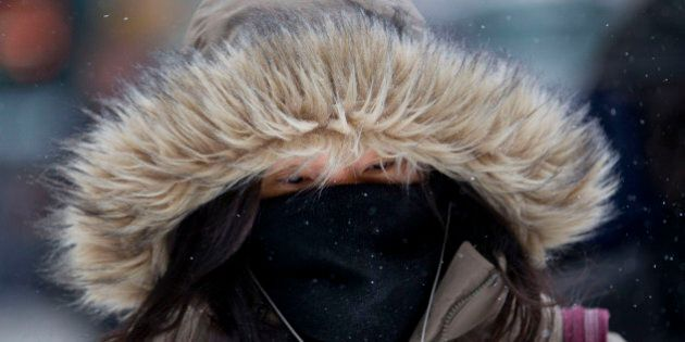 A pedestrian covers her face to keep warm in New York, U.S., on Friday, Jan. 3, 2014. Wind-driven snow...