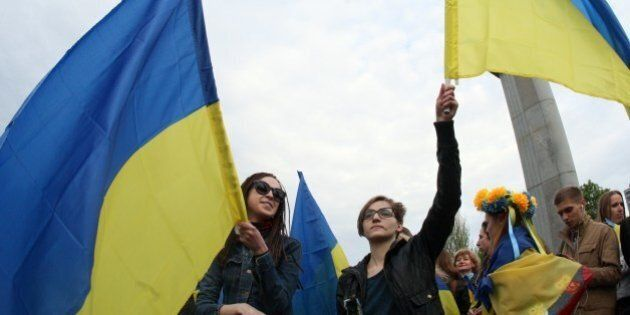 Women wave Ukrainian flags as they take part in a rally for national unity in the eastern Ukrainan city...