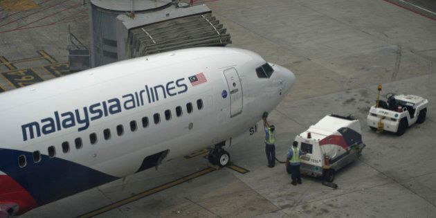 Workers inspect a Malaysia Airlines plane on the tarmac at Kuala Lumpur International Airport (KLIA)...