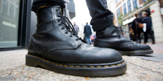 A pedestrian wearing Dr. Martens boots poses for a photograph outside the footwear company's store in...