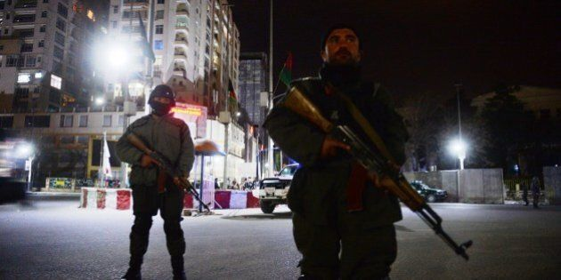 Afghan policemen block a road as they stands guard near the security perimeter setup around the Serena hotel in Kabul early on March 21, 2014. Security forces rushed to the luxury Serena hotel in central Kabul on March 20 evening after gunshots were heard at the venue, a high-security location favoured by foreign visitors to the Afghan capital. The gunfire at the hotel came on the same day that seven Taliban suicide attackers stormed a police station in the eastern city of Jalalabad killing 10 policemen. AFP PHOTO / SHAH MARAI        (Photo credit should read SHAH MARAI/AFP/Getty Images)