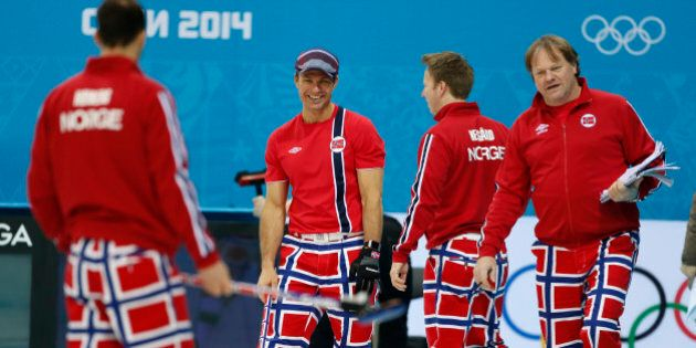 Norway skip Thomas Ulsrud, second from left, and teammate Torger Nergaard, second from right, share a...