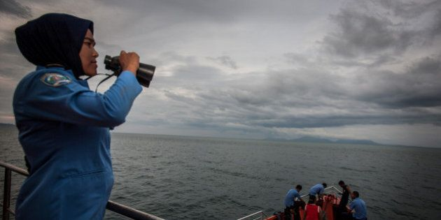 A personnel of Indonesia's National Search and Rescue looks over horizon during a search in the Andaman...
