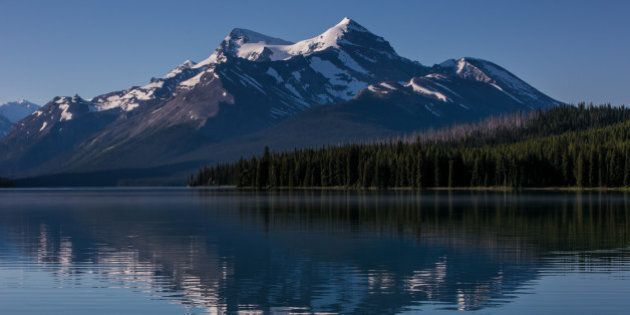 JASPER, CANADA - JUNE 30: The surrounding snowcapped mountains are reflected in Maligne Lake on June...
