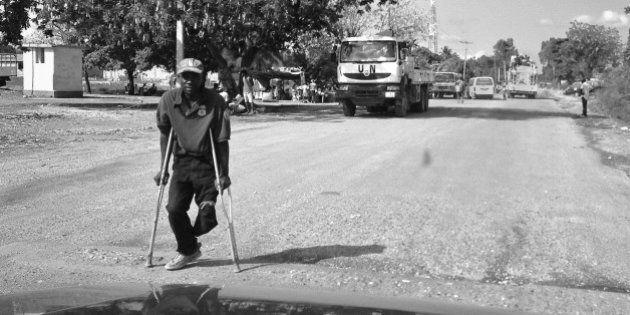 LEOGANE, HAITI - MARCH 20: A one-legged man hobbles along a ruined street March 20, 2013 in Leogane,...