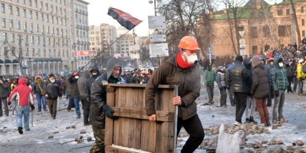 Protesters carry a wooden board to build barricades during clashes with the police in Kiev on January...