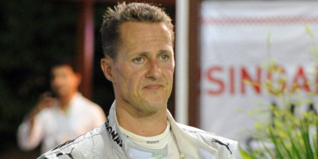 Mercedes AMG Petronas driver Michael Schumacher (L) of Germany walks back to the paddock after crashing out of Formula One's Singapore Grand Prix on September 23, 2012.    AFP PHOTO / ROSLAN RAHMAN        (Photo credit should read ROSLAN RAHMAN/AFP/GettyImages)