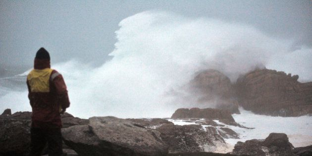 A man looks at waves crashing onto rocks as a storm brings heavy winds to Saint-Guenole, western France,...