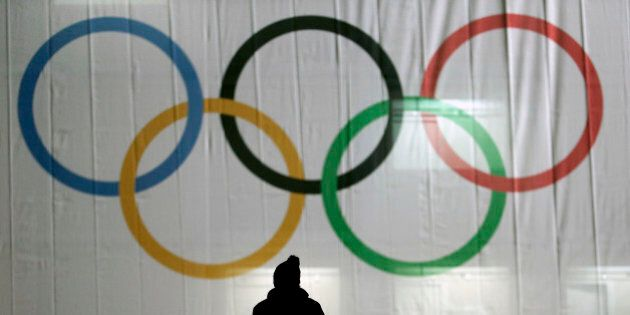 A man is silhouetted against the Olympic Rings as he walks to the venue for the women's normal hill ski...