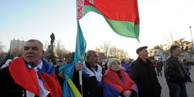 Pro-Russian activists hold (From L) the flags of Russia, Kazakhstan and Belarus during a gathering in...