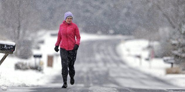 Sally Assmann runs through falling snow along Cambridge Drive in State College, Pa., Tuesday, Nov. 26,...
