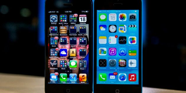 The home screen of an Apple Inc. iPhone 5 operating iOS 6, left, and an iPhone 5C operating iOS 7 is...