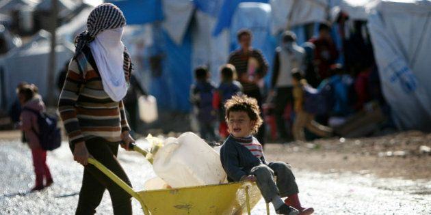 A Syrian-Kurdish refugee carries water containers on a wheelbarrow at the Quru Gusik (Kawergosk) refugee...