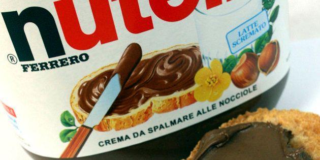 A knife spreads Fererro SpA's Nutella chocolate-hazelnut spread onto a piece of bread in Milan, Italy,...