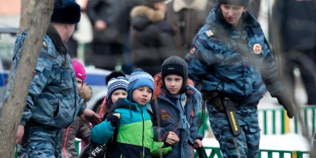 Police officers evacuate children from a Moscow school on Monday, Feb. 3, 2014. An armed teenager burst...