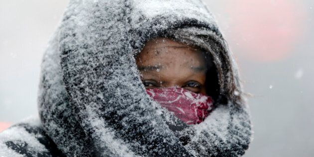 A woman stands at the entrance of a building during a winter snowstorm Tuesday, Jan. 21, 2014, in Philadelphia....