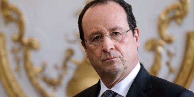 French President Francois Hollande listens to the speech of French Prime Minister during a new year ceremony...