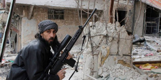 A rebel fighter from the Free Syrian Army holds a position with a Belgium made FAL rifle at a front line in the Salah al-Din neighbourhood of the northern Syrian city of Aleppo, on December 1, 2013. A Syrian regime air raid on the northern town of Al-Bab, in the Aleppo province, killed at least eleven people, in a second day of deadly strikes, the Syrian Observatory for Human Rights said. AFP PHOTO / MOHAMMED AL-KHATIEB        (Photo credit should read MOHAMMED AL-KHATIEB/AFP/Getty Images)
