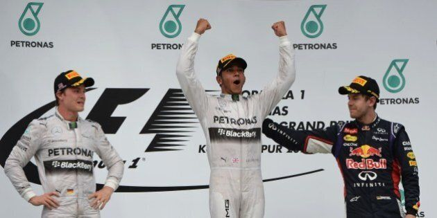 Mercedes driver Lewis Hamilton of Britain (C) celebrates his victory on the podium as second-placed Mercedes driver Nico Rosberg (L) and third-placed Red Bull driver Sebastian Vettel (R) look on at the awards ceremony after the Formula One Malaysian Grand Prix at the Sepang circuit near Kuala Lumpur on March 30, 2014. AFP PHOTO / ROSLAN RAHMAN (Photo credit should read ROSLAN RAHMAN/AFP/Getty Images)