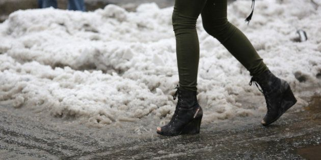 NEW YORK, NY - FEBRUARY 05: A woman with open toe boots navigates a slushy intersection near Union Square...