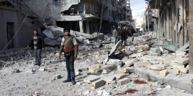 Syrians stand in a destroyed street following a reported airstrike by government forces on the northern...