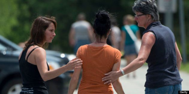 LAC-MEGANTIC QC - JULY 7: Two women reached out to another as she left the Polyvalente Montignac school...
