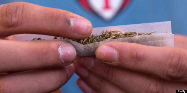 A young man rolls a marijuana joint during a demonstration demanding a new law on cannabis in Montevideo...