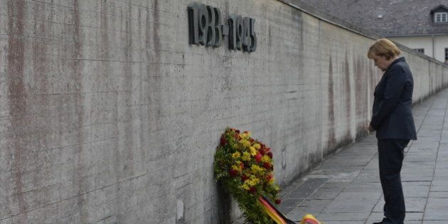 German Chancellor Angela Merkel pays respect during a wreath-laying ceremony at the wall of the Concentration...