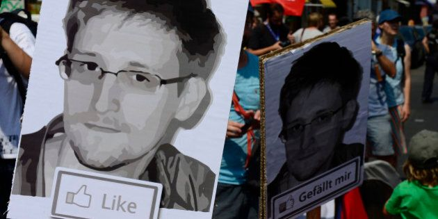 Demonstrators hold placards featuring an image of former US intelligence contractor Edward Snowden as...
