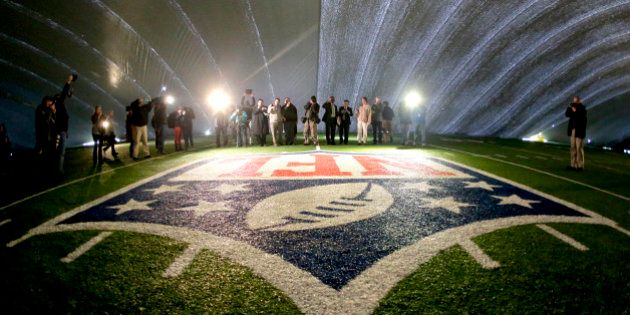 In this photograph taken with a fisheye lens, the NFL logo at midfield of MetLife Stadium is illuminated...