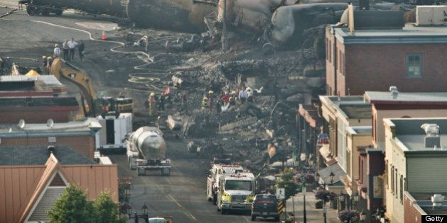 LAC-MEGANTIC QC - JULY 8: Search teams carry a large white bag out of the rubble in the town centre of...