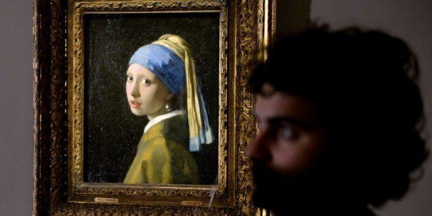 A woman stands next to the masterpiece 'Girl with a Pearl Earring' by Dutch painter Johannes Vermeer...