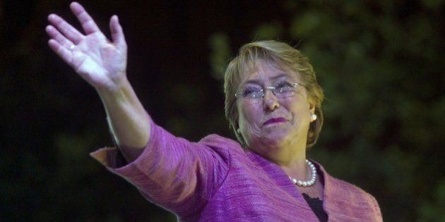 Chilean presidential candidate for the New Majority coalition, Michelle Bachelet, waves as she celebrates...
