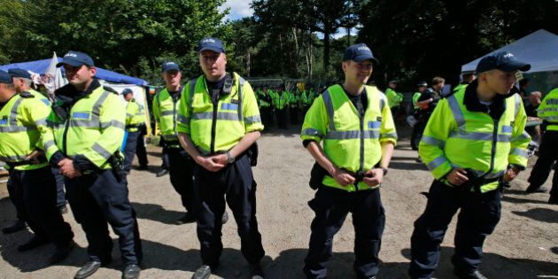 British police officers guard the entrance to a fracking site in Balcombe, West Sussex, England, as anti...