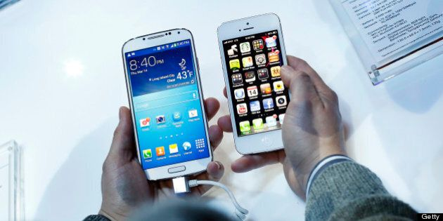 An attendee holds a Samsung Electronics Co. Galaxy S4 smartphone, left, next to an Apple Inc. iPhone...
