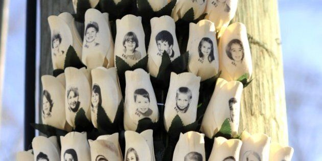 Roses with the faces of the Sandy Hook Elementry students and adults killed are seen on a pole in Newtown,...