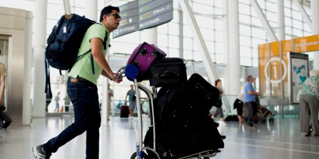 A traveler pushes a cart of luggage at Toronto Pearson International Airport in Toronto, Ontario, Canada,...