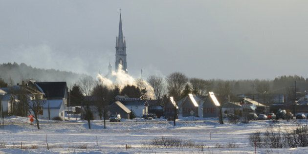 Smoke rises from the burnt remains of a retirement home in L'Isle-Verte on January 23, 2014. Firefighters...